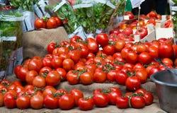 Tomates rouges mûres juteuses à vendre à un marché végétal Photo libre de droits