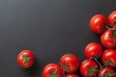 Tomates rouges sur le noir Images stock