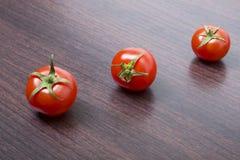 Tomates rouges sur une table brune en bois Trois tomates-cerises rouges Photos libres de droits