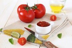 Tomates, salsa de tomate de tomate y aceite de oliva maduros Fotos de archivo libres de regalías