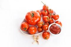 Tomates, salsa de tomate y ajo aislados en el fondo blanco foto de archivo libre de regalías
