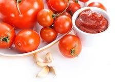 Tomates, salsa de tomate y ajo aislados en el fondo blanco imagenes de archivo