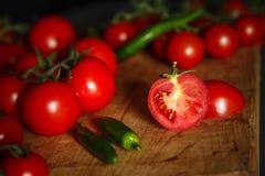 Tomates sur en bois avec des pappers verts Photos libres de droits