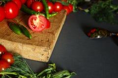 Tomates sur en bois avec des pappers verts Photographie stock libre de droits