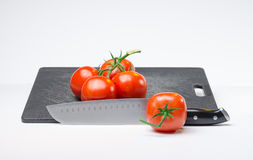 Tomates sur la planche à découper images stock