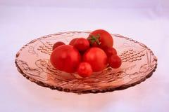 Tomates sur le bol de fruit en verre rose photos libres de droits