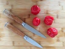Tomates sur le conseil en bambou avec des couteaux photo libre de droits