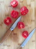 Tomates sur le conseil en bambou avec des couteaux image stock