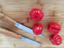 Tomates sur le conseil en bambou avec des couteaux photos stock