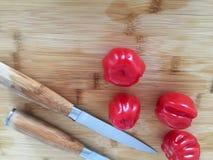 Tomates sur le conseil en bambou avec des couteaux image libre de droits