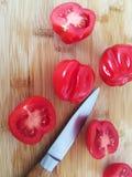Tomates sur le conseil en bambou avec des couteaux photographie stock libre de droits