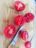 Tomates sur le conseil en bambou avec des couteaux photo stock