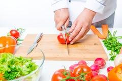 Tomates sur une planche à découper dans les mains photos libres de droits