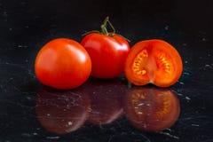 Tomates sur une table noire Image libre de droits