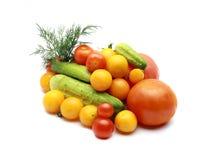 Tomates, tomates de cereja vermelhos e amarelos, pepino, no fundo branco Fotos de Stock