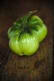 Tomates verdes de la carne de vaca en una tabla de madera oscura Fotos de archivo