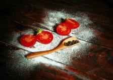 Tomates vermelhos ao lado das pimentas na placa de madeira fotos de stock royalty free