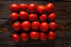 Tomates vermelhos com gotas da água Tomates de variedades diferentes fundo dos omatoes Conceito saudável do alimento dos tomates  Foto de Stock