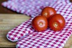 Tomates vermelhos em uma toalha de cozinha vermelha Foto de Stock Royalty Free