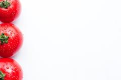 Tomates vermelhos frescos com gotas em um fundo branco Fotografia de Stock Royalty Free