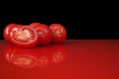 Tomates vermelhos frescos de Roma na tabela vermelha e no fundo preto, cópia Fotografia de Stock