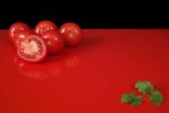 Tomates vermelhos frescos de Roma na tabela vermelha e no fundo preto, cópia Fotografia de Stock Royalty Free
