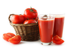 Tomates vermelhos frescos no suco da cesta e de tomate no vidro isolado em um branco Foto de Stock Royalty Free