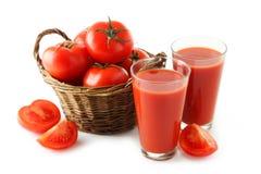 Tomates vermelhos frescos no suco da cesta e de tomate no vidro isolado em um branco Fotos de Stock Royalty Free