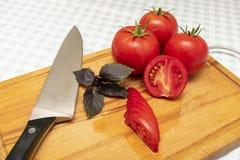 Tomates vermelhos maduros com um ramo da manjericão e da faca fotos de stock