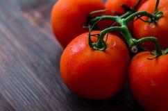 Tomates vermelhos maduros em um fundo de madeira Foto de Stock