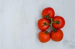 Tomates vermelhos maduros em um fundo de madeira Fotografia de Stock Royalty Free