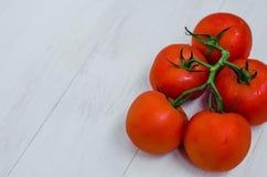 Tomates vermelhos maduros em um fundo de madeira Fotografia de Stock
