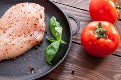 Tomates vermelhos maduros em uma tabela de madeira ao lado de uma frigideira em que uma faixa crua fresca da galinha é polvilhada imagem de stock royalty free