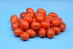 Tomates vermelhos pequenos em um fundo azul Imagens de Stock