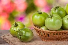 Tomates vertes non mûres dans un panier en osier sur la table en bois avec le fond brouillé Photographie stock