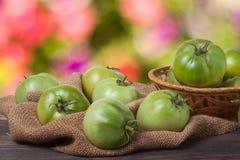 Tomates vertes non mûres dans un panier en osier sur la table en bois avec le fond brouillé Images libres de droits
