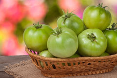 Tomates vertes non mûres dans un panier en osier sur la table en bois avec le fond brouillé Photo libre de droits