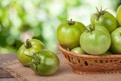 Tomates vertes non mûres dans un panier en osier sur la table en bois avec le fond brouillé Photographie stock libre de droits