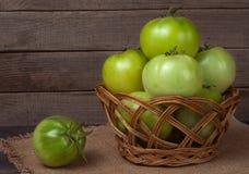 Tomates vertes non mûres dans un panier en osier sur la table en bois avec renvoyer Image stock