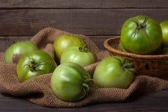 Tomates vertes non mûres dans un panier en osier sur la table en bois avec renvoyer Images libres de droits
