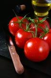 Tomates y aceite de oliva maduros en fondo negro Imagen de archivo