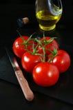 Tomates y aceite de oliva maduros en fondo negro Fotos de archivo