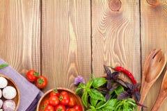Tomates y albahaca frescos de los granjeros en la tabla de madera Foto de archivo libre de regalías