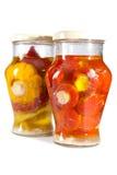 Tomates y calabazas y verdura adobados del arbusto en un tarro de cristal. Aún-vida en un fondo blanco Imagen de archivo libre de regalías