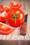 Tomates y cuchillo frescos Imagenes de archivo