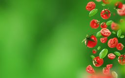 Tomates y hojas de cereza que caen del aire foto de archivo