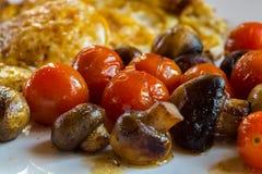 Tomates y huevo de Muschrooms en una placa blanca Fotos de archivo