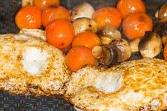 Tomates y huevo de Muschrooms que cocinan en un sartén Foto de archivo