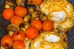 Tomates y huevo de Muschrooms que cocinan en un sartén Fotografía de archivo