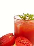 Tomates y jugo en vidrio Fotos de archivo libres de regalías